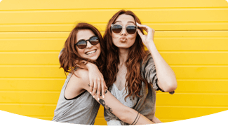 2 girls laughing in front of yellow wall