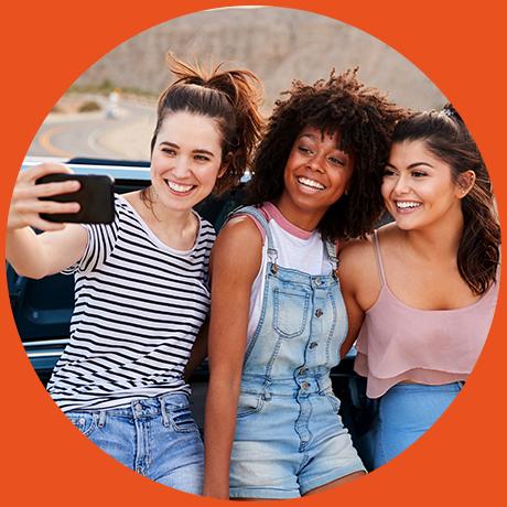 girls taking selfie by car