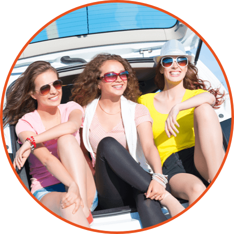 Three girls sitting on boot of car