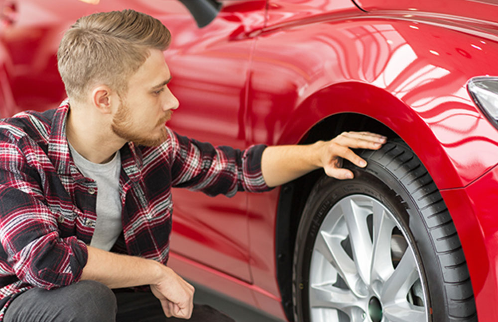 Young man looking at car