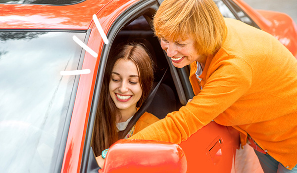 Mum talking to daughter who is sat in car