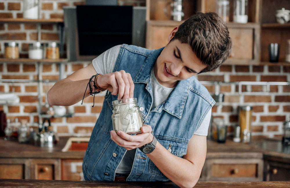 Boy saving money in jar