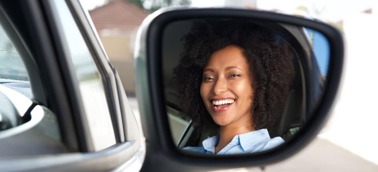 Girl looking in car mirror