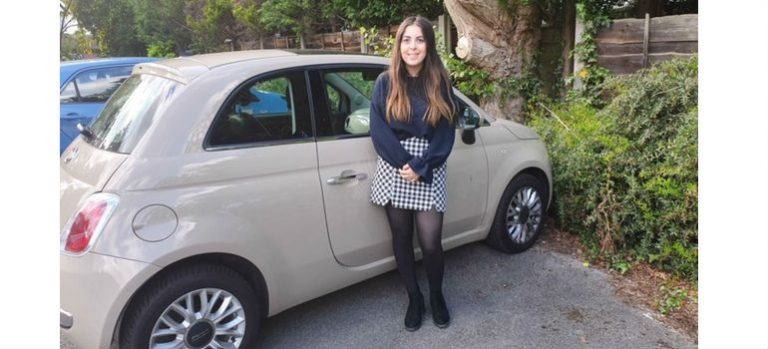 happy girl stood next to car